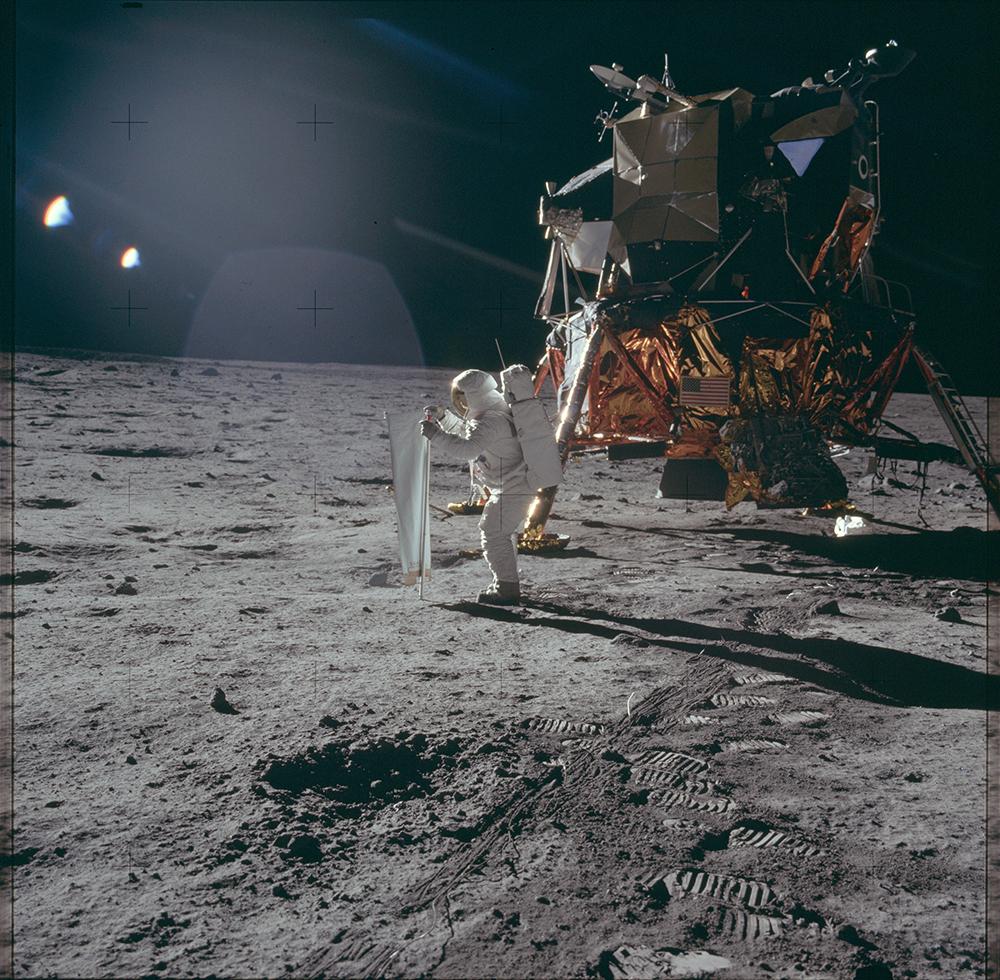 Astronaut Edwin «Buzz» Aldrin entrollt das Sonnenwindsegel der Universität Bern auf dem Mond.  Bild: NASA Apollo Image Archive