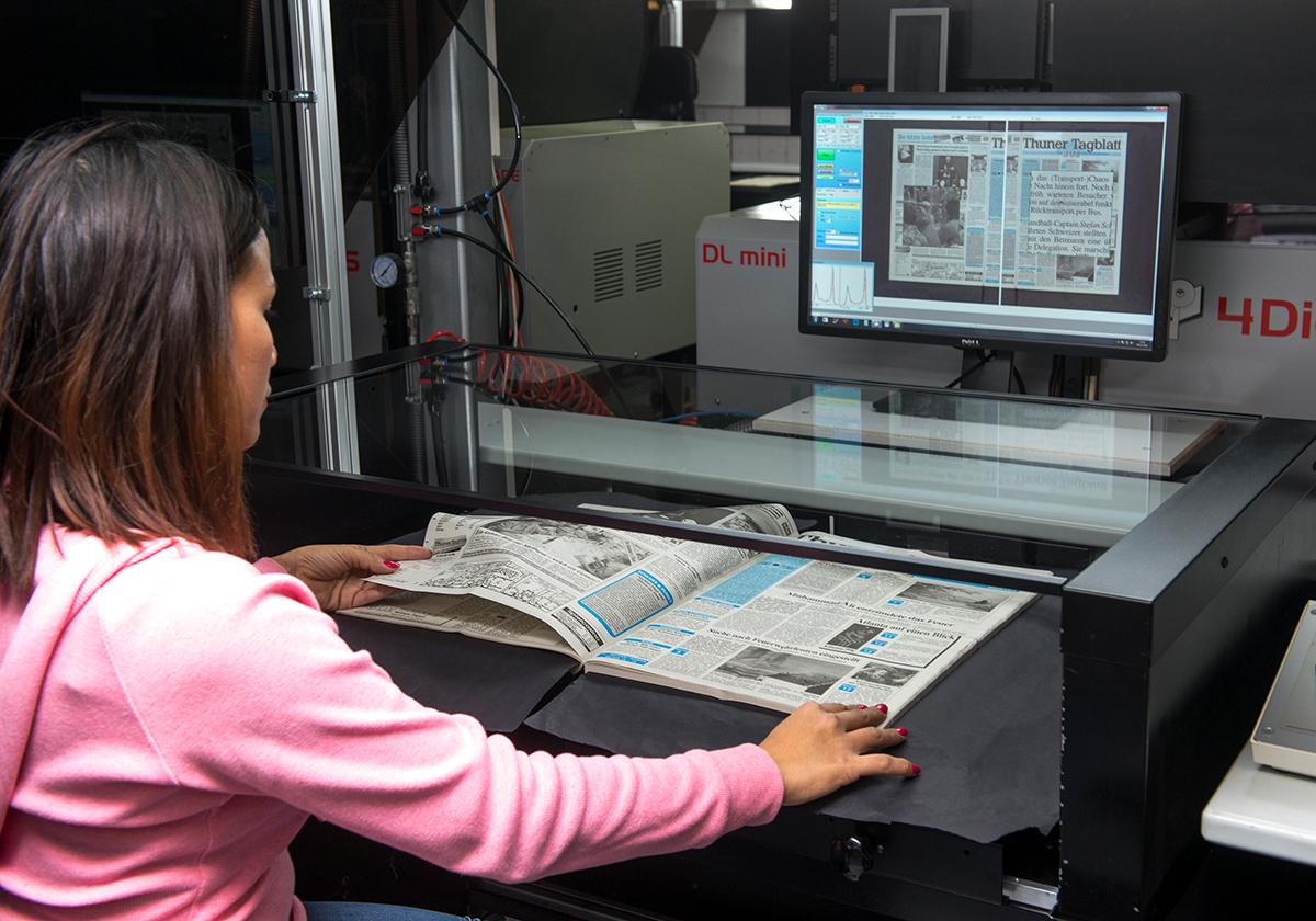 Die Mitarbeiterin einer Scanfirma scannt einen Band des «Thuner Tagblatts». Dabei blättert sie die Seiten von Hand um, fährt die Glasplatte auf das Papier, damit sie Seiten flach liegen, und fotogafiert immer eine Doppelseite.
